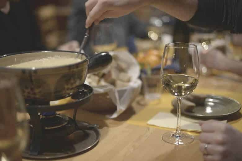 fondue cheese non the table with white wine