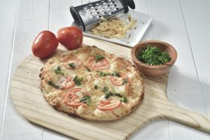 round pizza on a wooden pizza tray. There are 2 red tomatoes, grated cheese and coriander