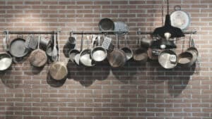 Several different cookware hangs on the wall