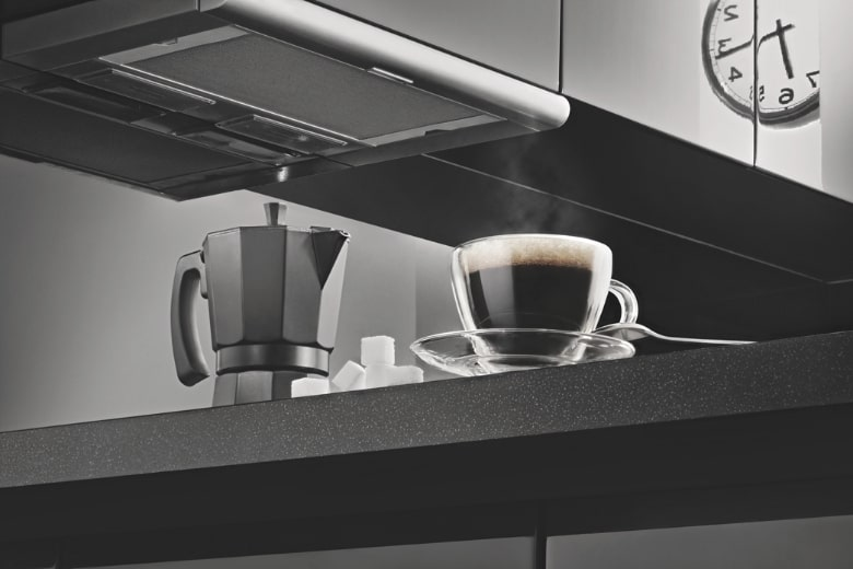 a black electric coffee percolators with a cup of coffee