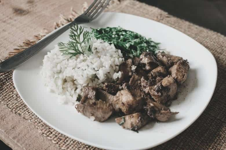 some rice and meat on a white plate