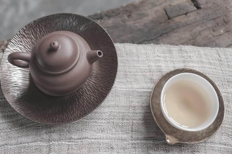 brown tea kettle and a cup