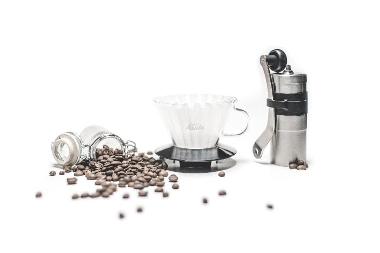 coffee grinder beside coffee filter and some beans