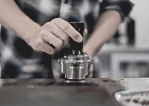 big coffee grinder, a man making coffee