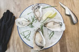 a plate of oysters and a oyster knife