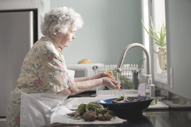 older woman washing vegetables with touchless faucet
